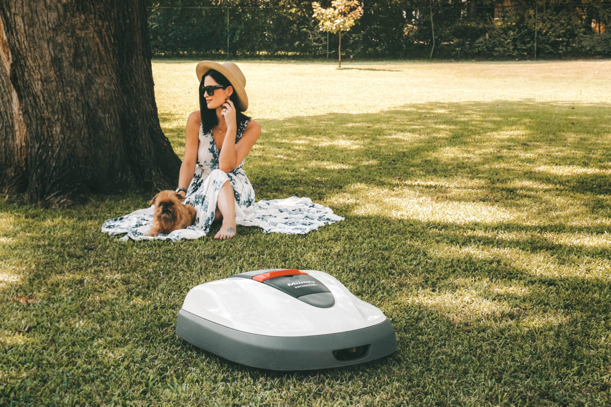 Honda Miimo Robotic Lawn Mower Review by popular Austin lifestyle blog, Dressed to Kill: image of woman and her dog sitting near the Honda Miimo Robotic Lawn Mower.