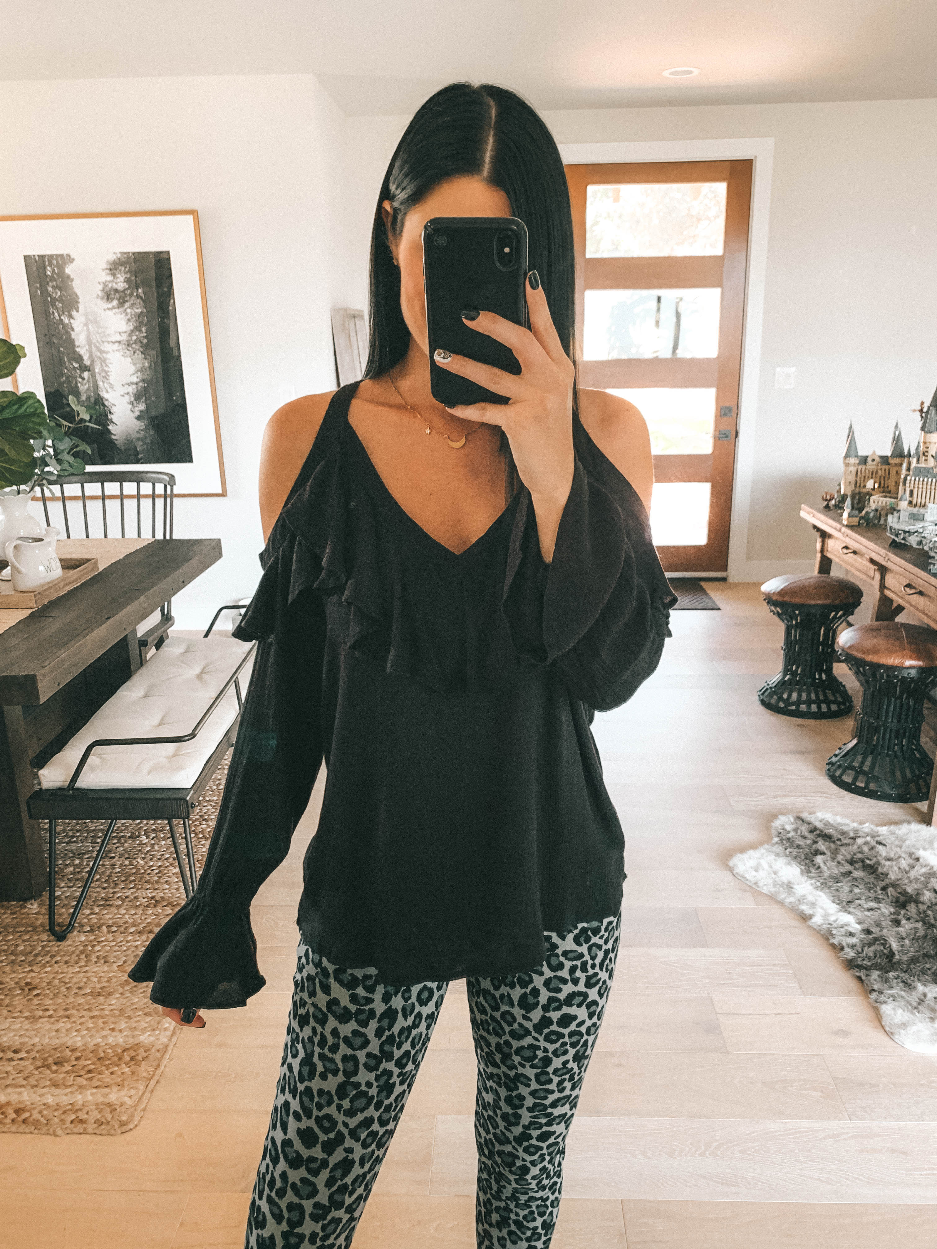 7 Affordable Fall Outfits from Walmart by popular Austin fashion blog, Dressed to Kill: image of a woman standing inside her house and wearing a black Walmart Sofia Jeans Cold-Shoulder Ruffle Neck Woven Top and Sofia Jeans Sofia Skinny Leopard Print Mid Rise Stretch Ankle Jean.