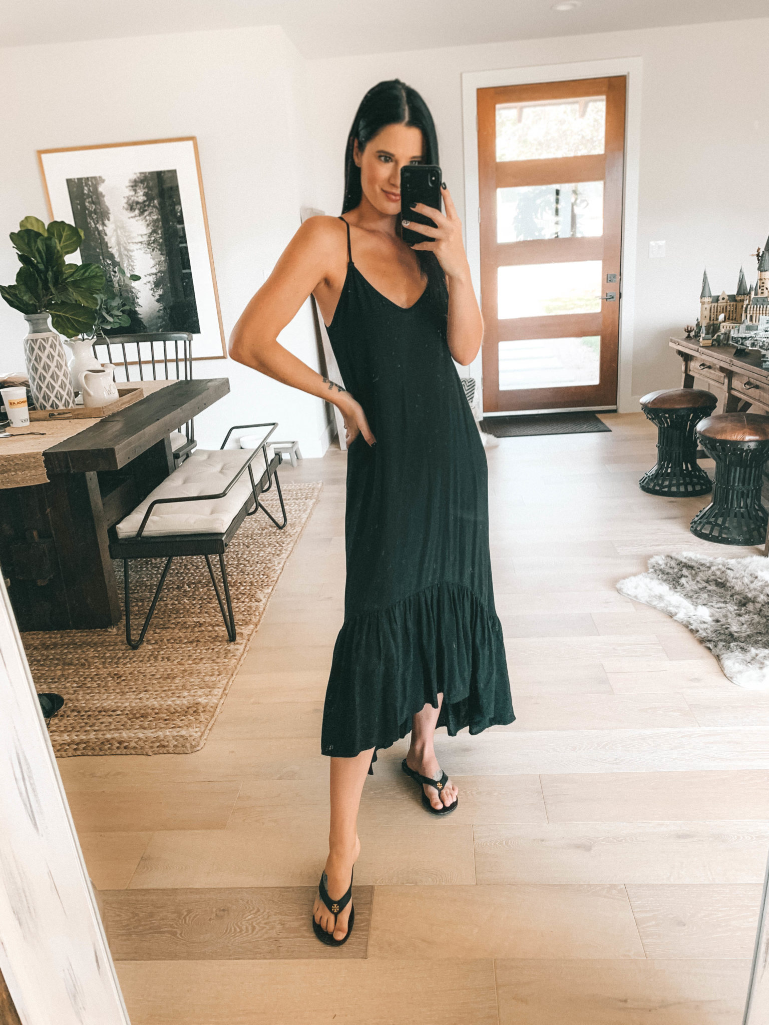 7 Affordable Fall Outfits from Walmart by popular Austin fashion blog, Dressed to Kill: image of a woman standing inside her house and wearing a black Walmart Love Sadie Women's Ruffle Maxi Dress.