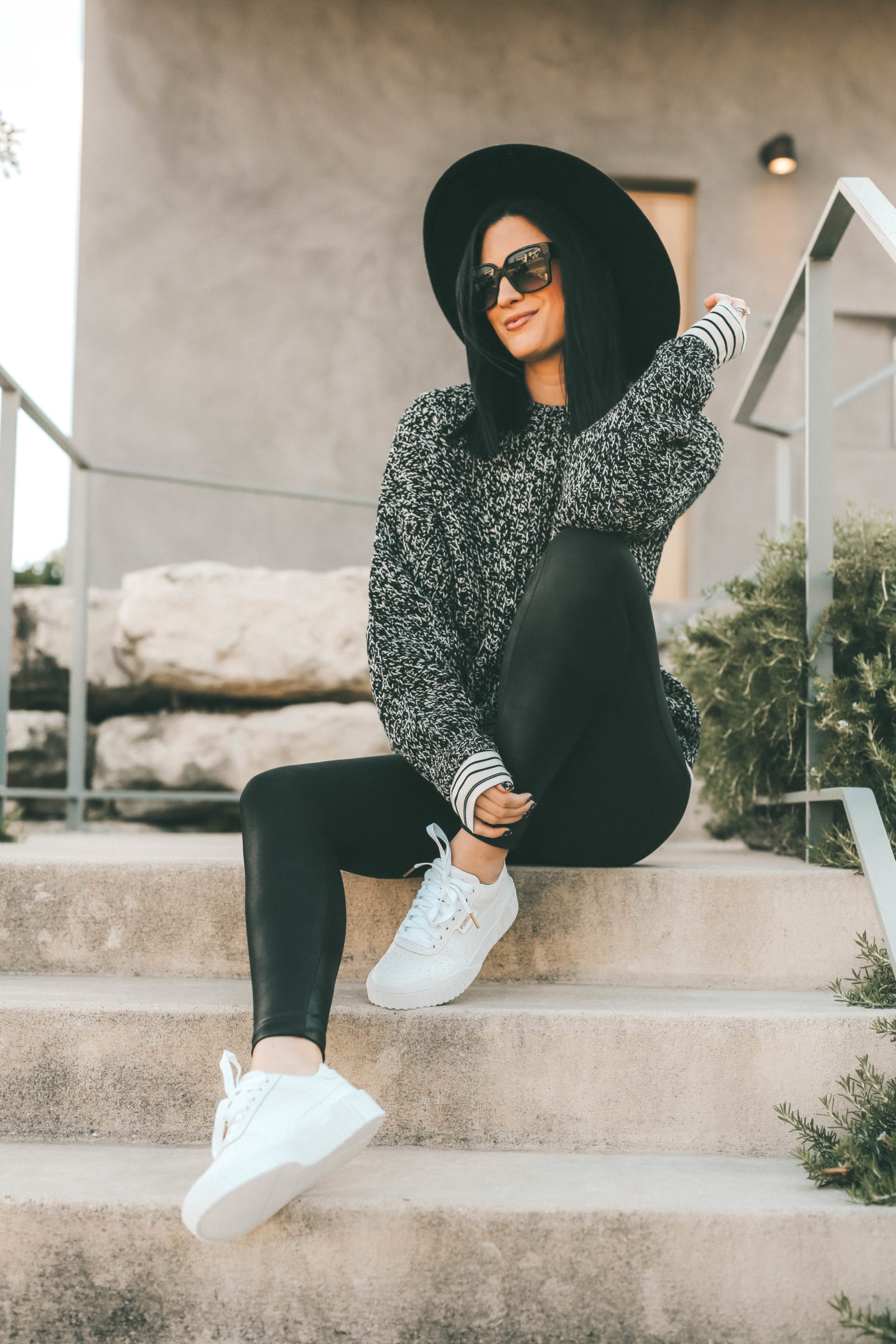 How to Wear White Sneakers by popular fashion blog, Dressed to Kill: image of a woman wearing a TopShop black and white sweater, black felt hat, black leggings, and white Puma sneakers.