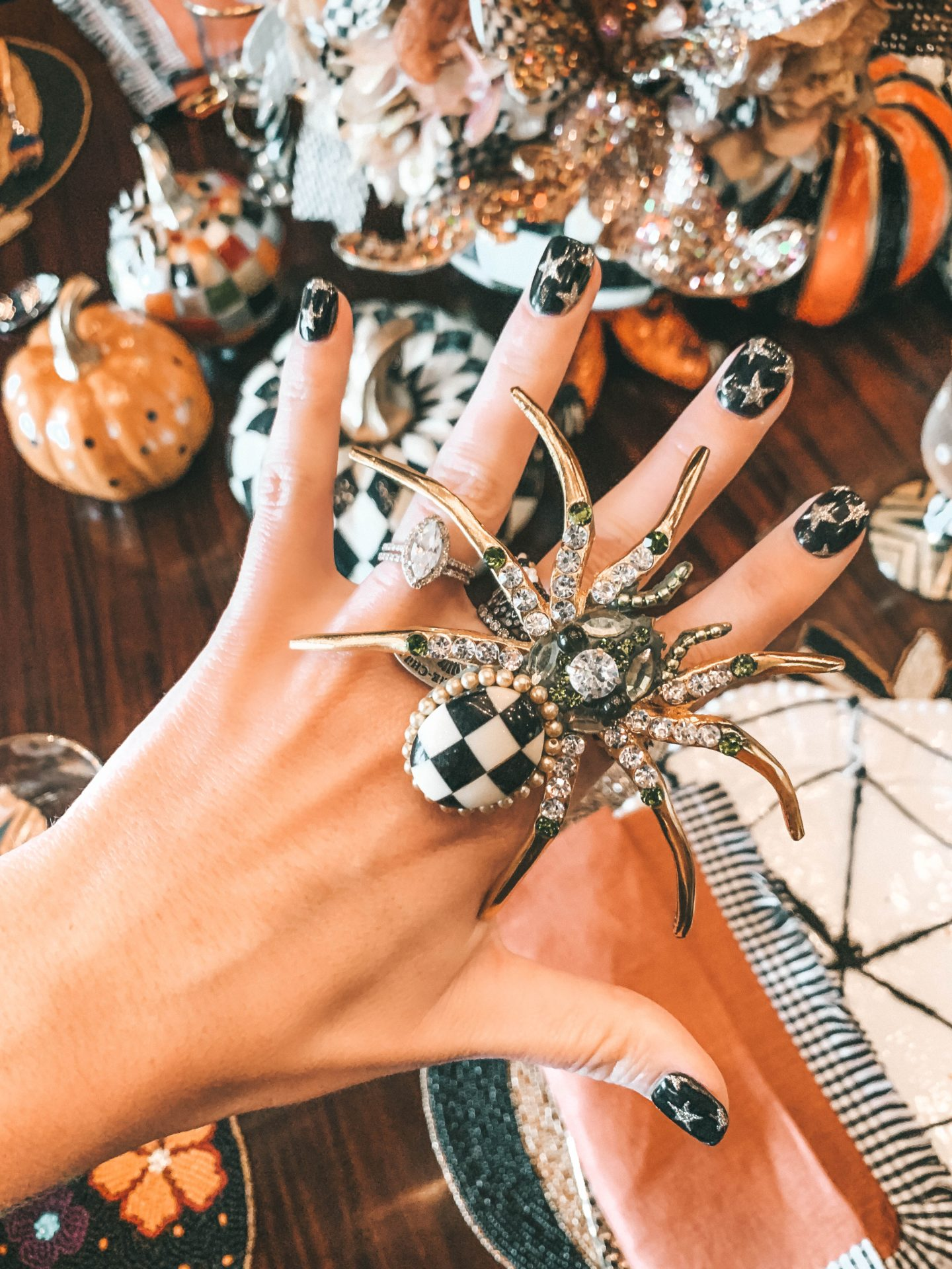 MacKenzie-Childs Halloween Home Decor by popular life and style blog, Dressed to Kill: image of a woman wearing a giant MacKenzie Childs spider napkin ring.