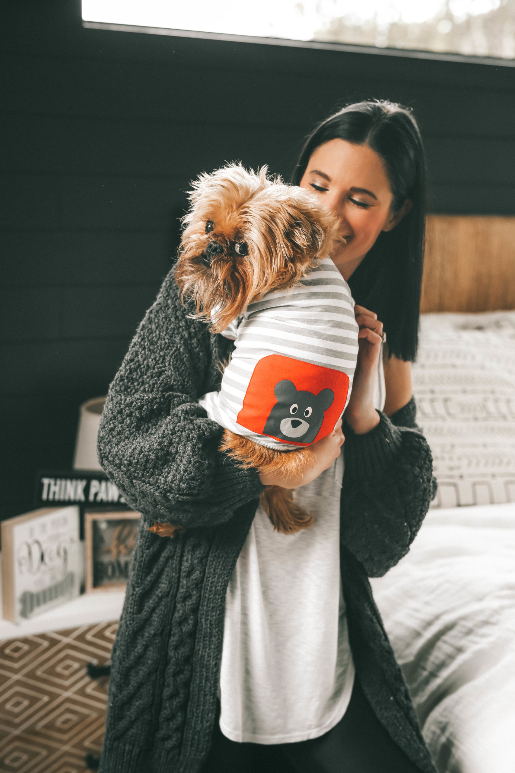 How to Pamper Your Pet by popular Nashville life and style blog, Dressed to Kill: image of a woman holding a dog wearing a stripped outfit from Tuesday Morning.