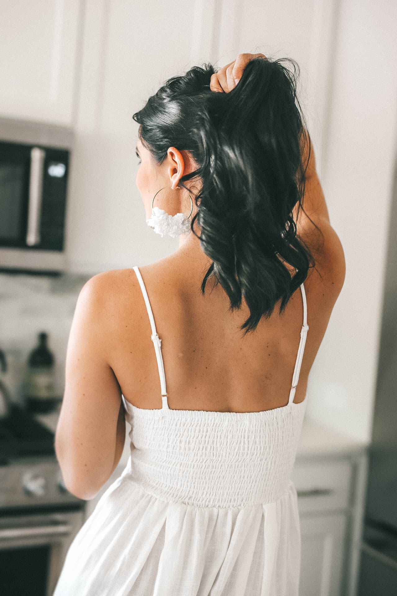 Best Hair Growth Products by popular Austin beauty blog, Dressed to Kill: image of a woman wearing a white spaghetti strap dress and white pom earrings and holding her hair up in her hand.