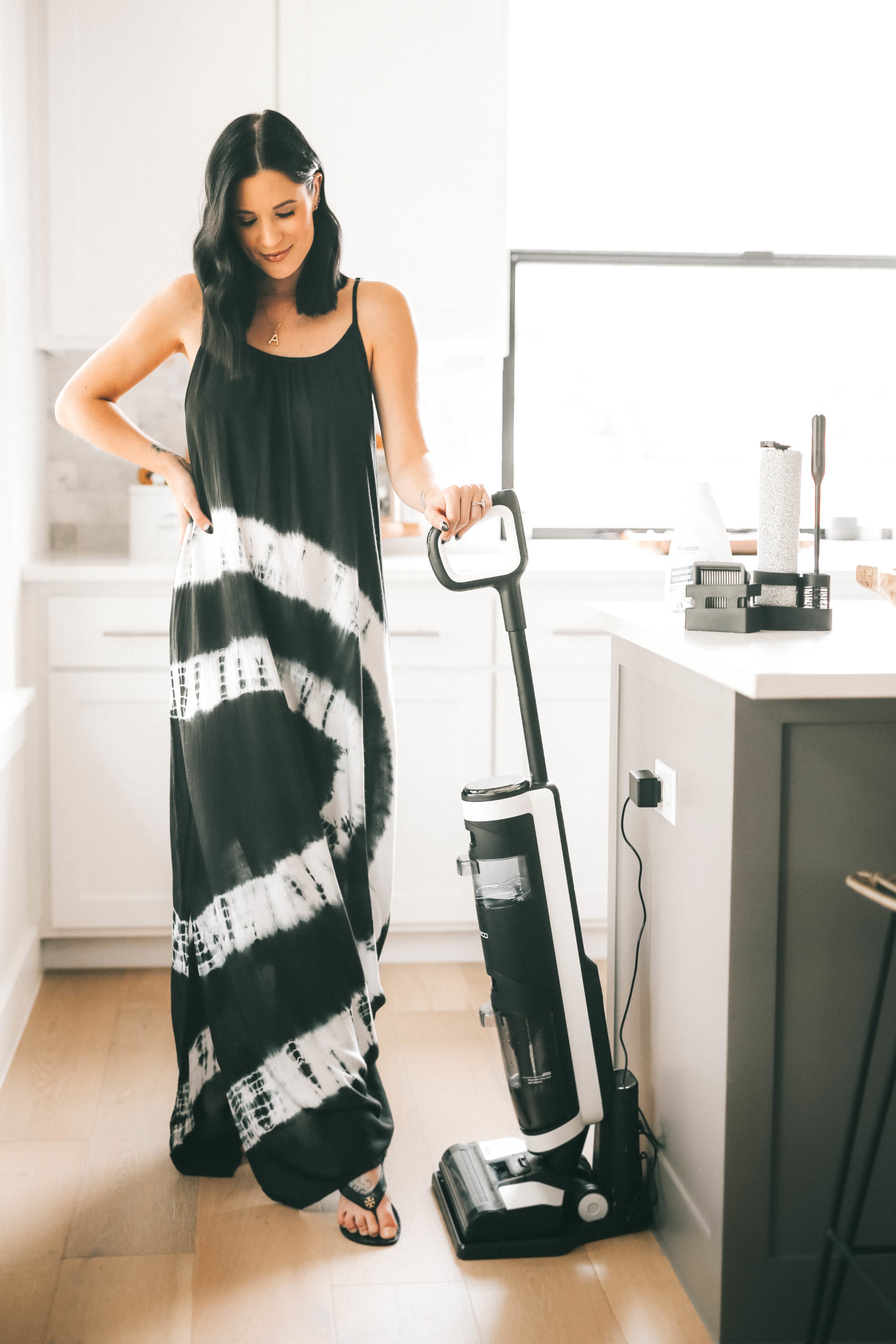 Tineco Floor One S3 by popular Austin lifestyle blog, Dressed to Kill: image of a woman wearing a black and white tie dye maxi and standing in her kitchen next to a Tineco Floor One S3 vacuum.