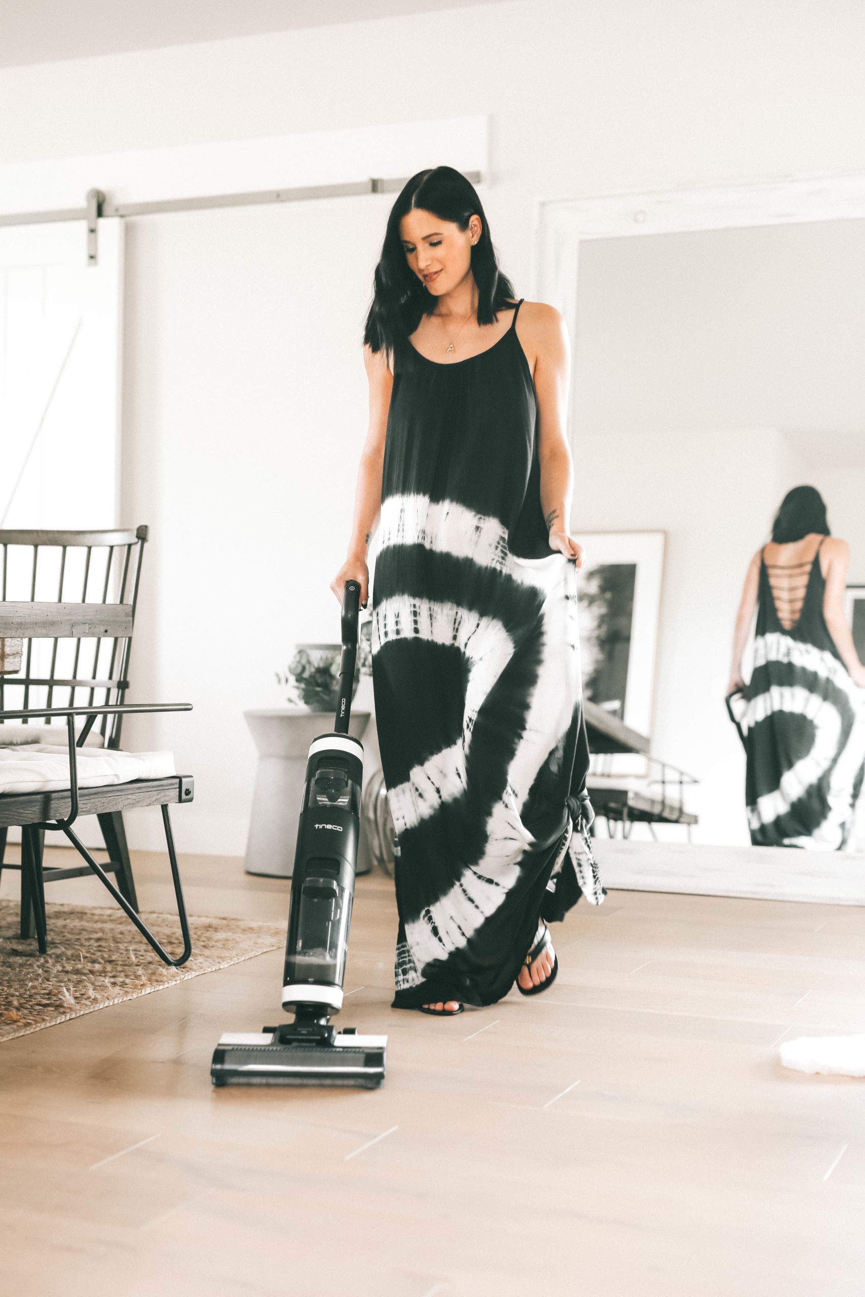 Tineco Floor One S3 by popular Austin lifestyle blog, Dressed to Kill: image of a woman wearing a black and white tie dye maxi and using a Tineco Floor One S3 vacuum in her kitchen.