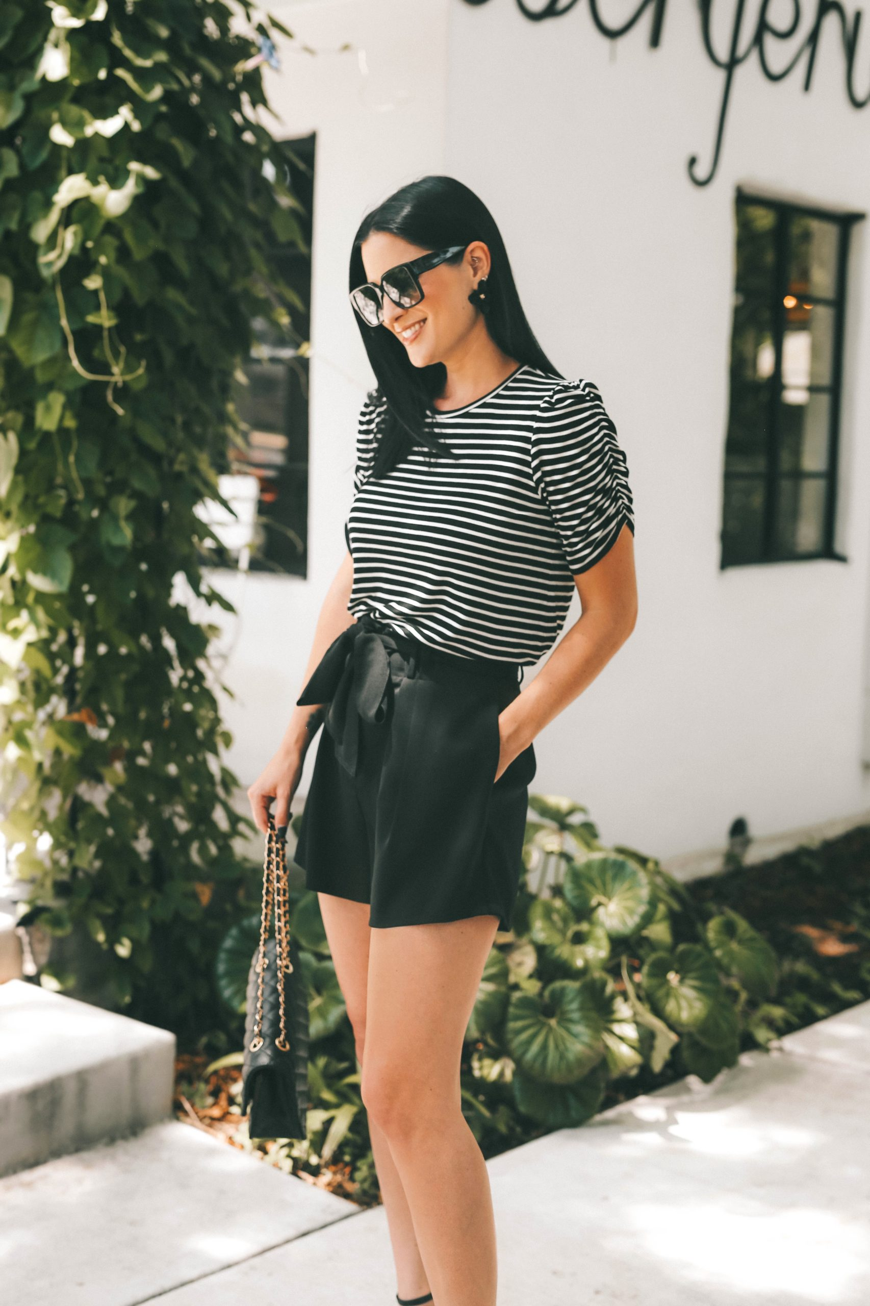 Gibson Look Road Trip by popular Austin fashion blog, Dressed to Kill: image of a woman wearing a pair of black paper bag shorts and a black and white stripe top.