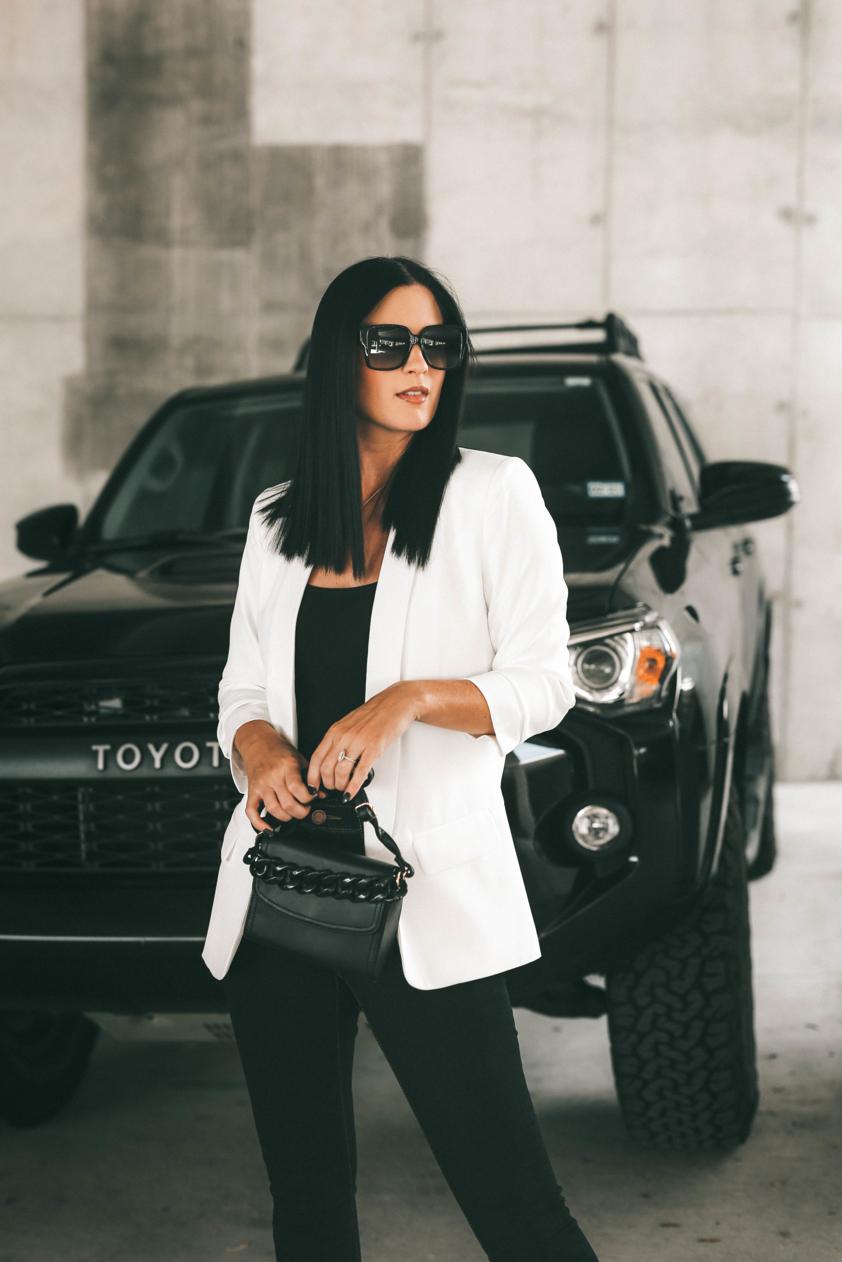 Blazer for Women by popular Austin fashion blog, Dressed to Kill: image of a woman standing in front of her black Toyota car and wearing a Walmart Scoop Scrunch Sleeve Shawl Collar Blazer, Jordache Women's Essential High Rise Super Skinny Jean, Guess Womens Simi Adjustable Straps V-Back Bodysuit, black frame sunglasses, and holding a black purse.