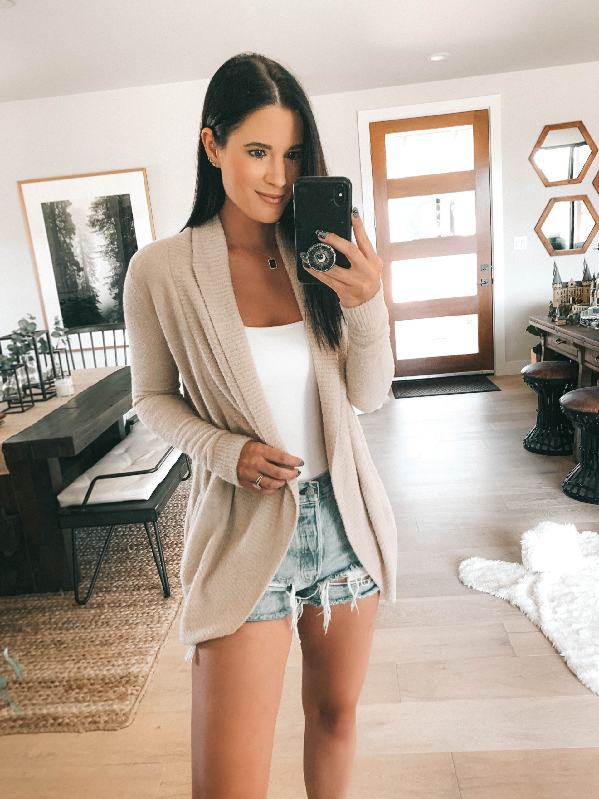 Nordstrom Anniversary Sale by popular Austin fashion blog, Dressed to Kill: image of a woman wearing Nordstrom CozyChic Lite® Circle Cardigan BAREFOOT DREAMS®, Nordstrom Pax Ripped High Waist Denim Shorts BDG URBAN OUTFITTERS, and Nordstrom Cami Bodysuit BP..