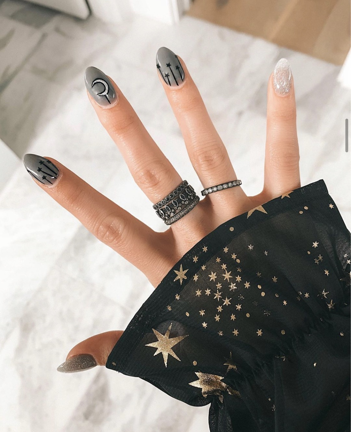 Nail Art Designs by popular Austin beauty blog, Dressed to Kill: image of a woman with grey and black moon and stars nail art.