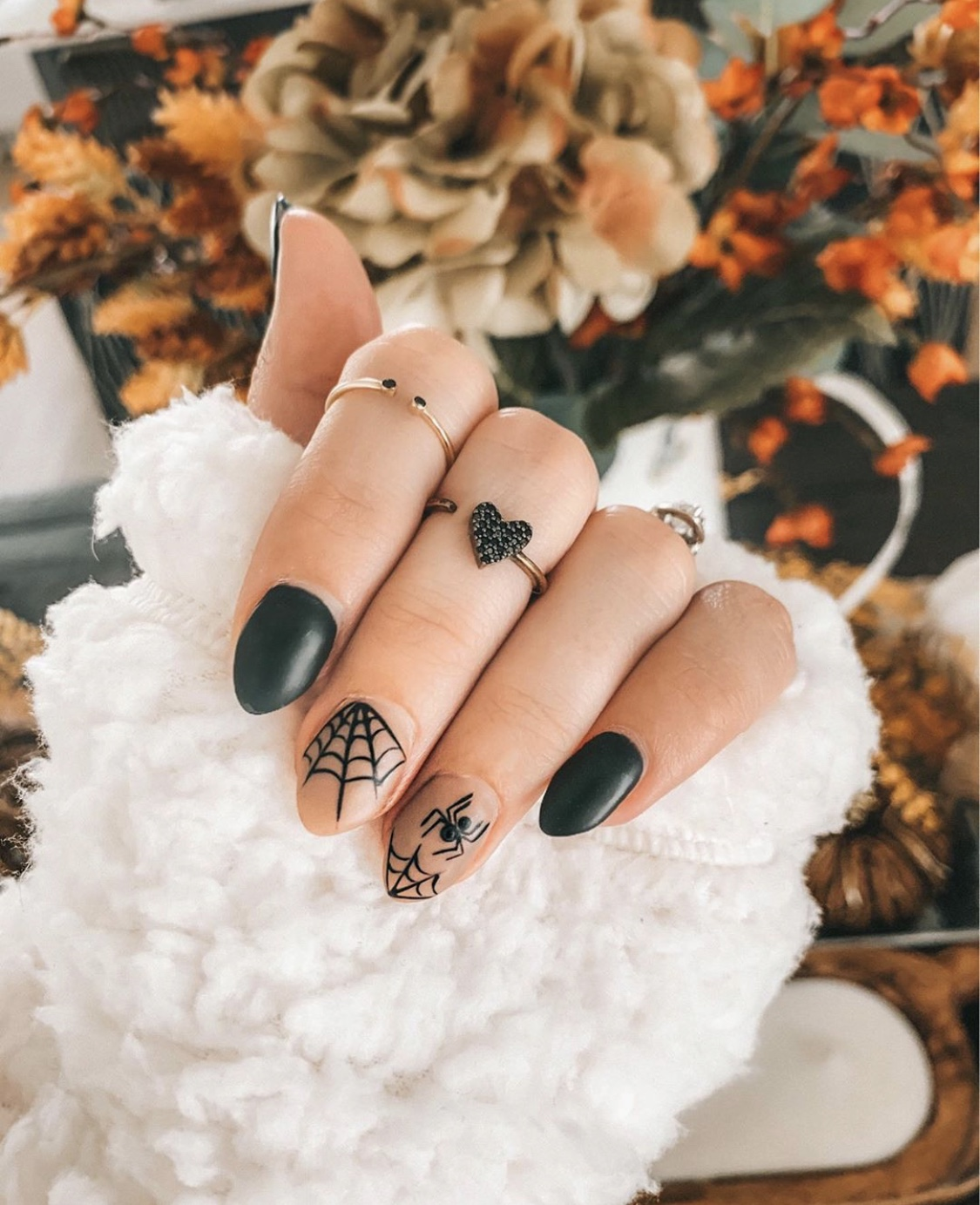 Nail Art Designs by popular Austin beauty blog, Dressed to Kill: image of a woman with spider design nail art and wearing Mejuri rings.