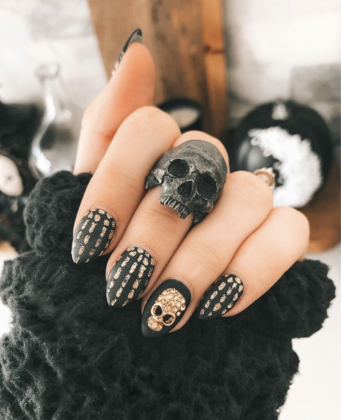 Nail Art Designs by popular Austin beauty blog, Dressed to Kill: image of a woman with gold and black skeleton design nail art and wearing a Into the Fire skull ring.