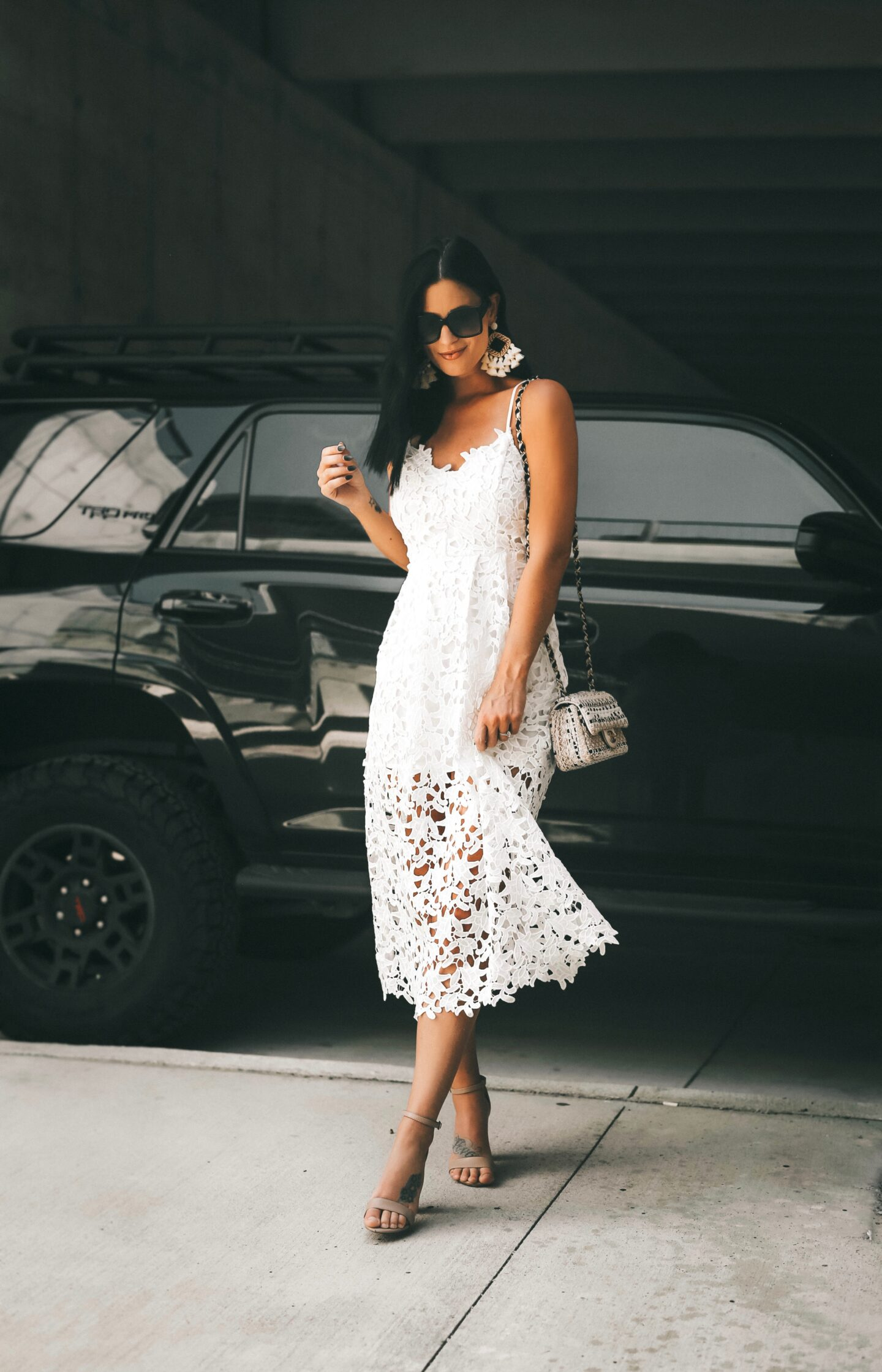 Online Discount Codes by popular Austin life and style blog, Dressed to Kill: image of a woman standing in a parking garage next to a black car and wearing a white lace strapless dress.