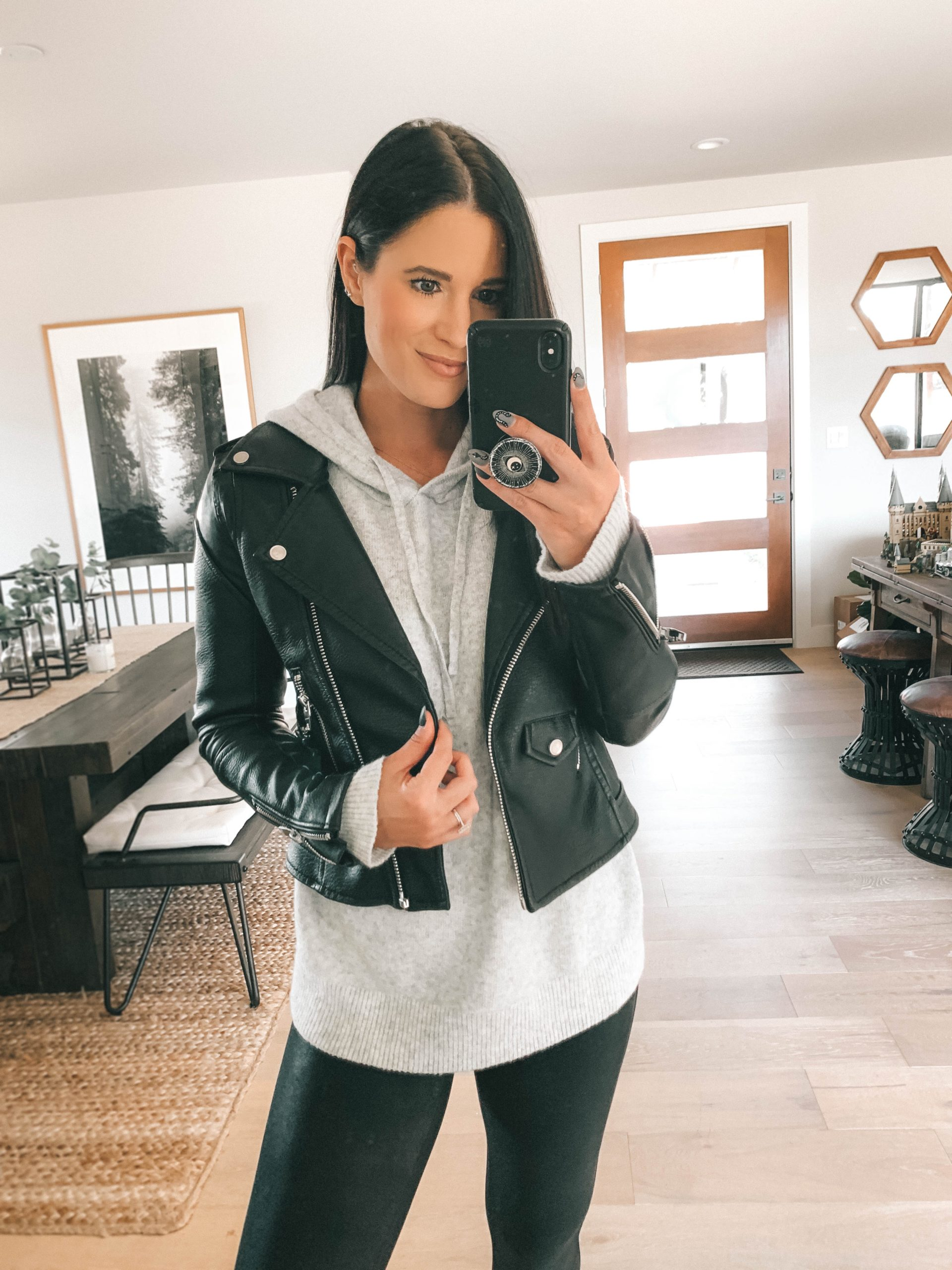 Nordstrom Anniversary Sale by popular Austin fashion blog, Dressed to Kill: image of a woman wearing a black faux leather jacket, grey hoodie sweater, and black faux leather leggings.