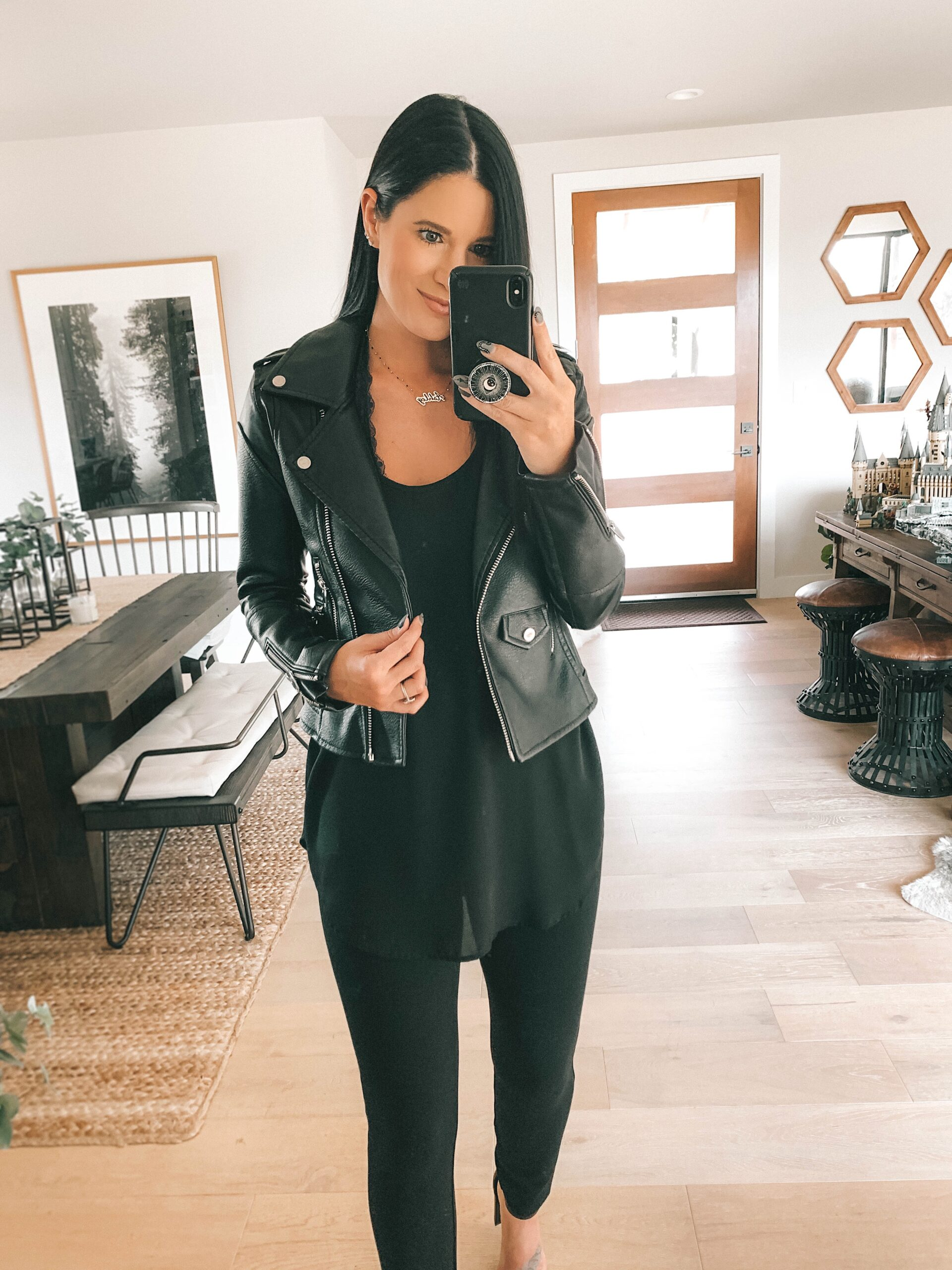 Nordstrom Anniversary Sale by popular Austin fashion blog, Dressed to Kill: image of a woman wearing a black faux letter jacket, black top, and black leggings.