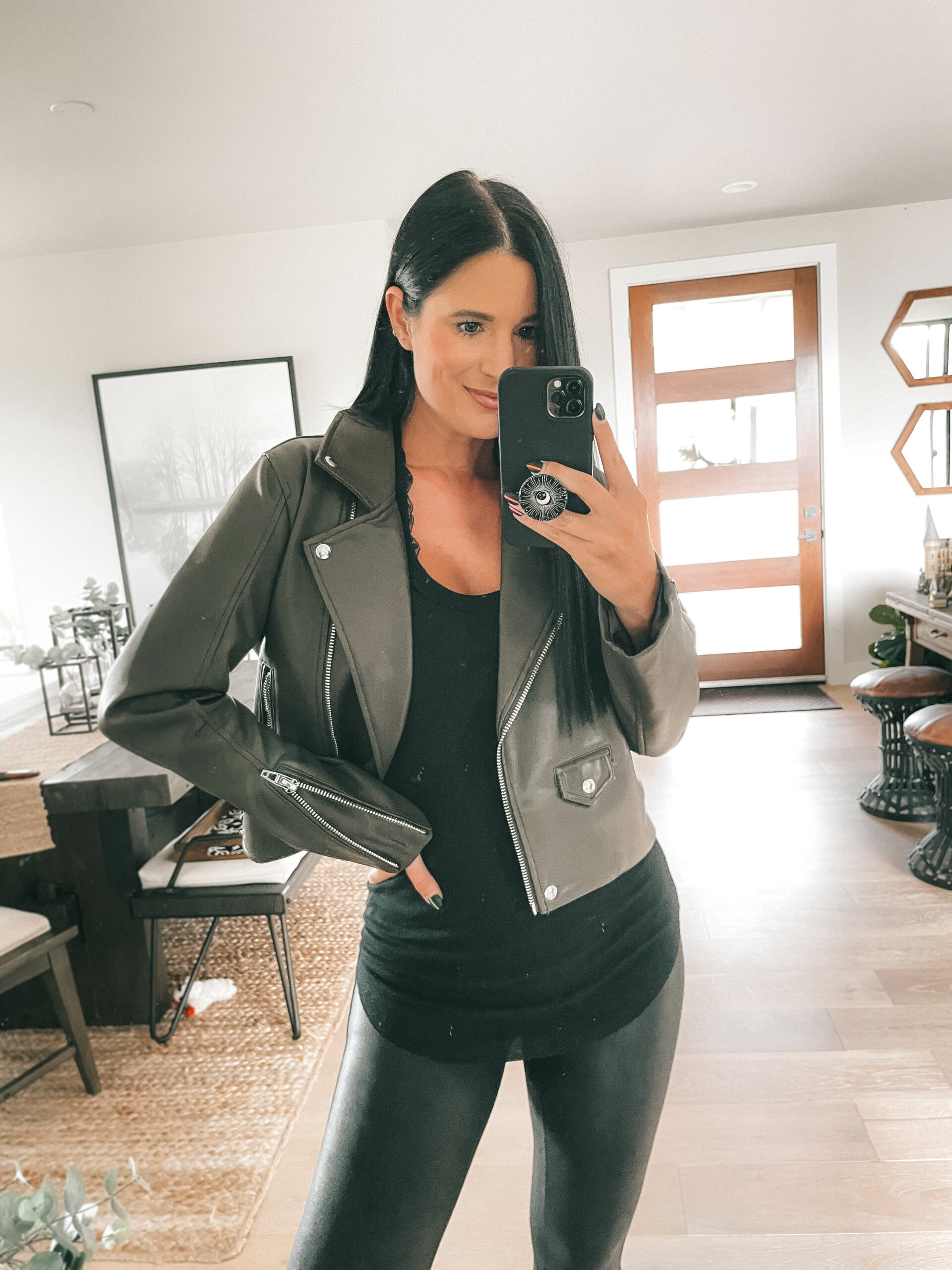 Nordstrom Anniversary Sale by popular Austin fashion blog, Dressed to Kill: image of a woman wearing a grey faux leather jacket, black top, and black faux leather leggings.