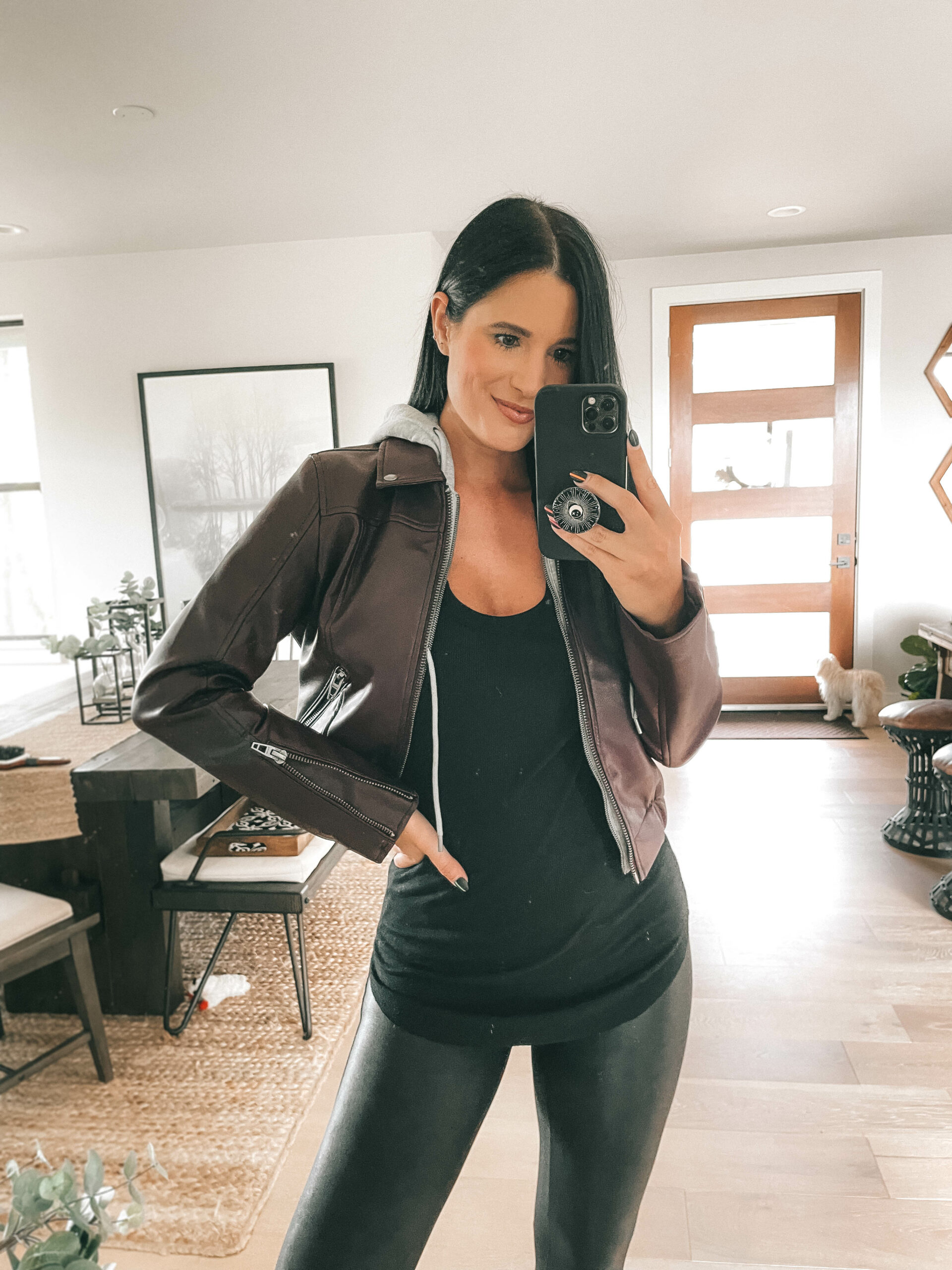 Nordstrom Anniversary Sale by popular Austin fashion blog, Dressed to Kill: image of a woman wearing a black faux leather hooded jacket, black top and black faux leather leggings.
