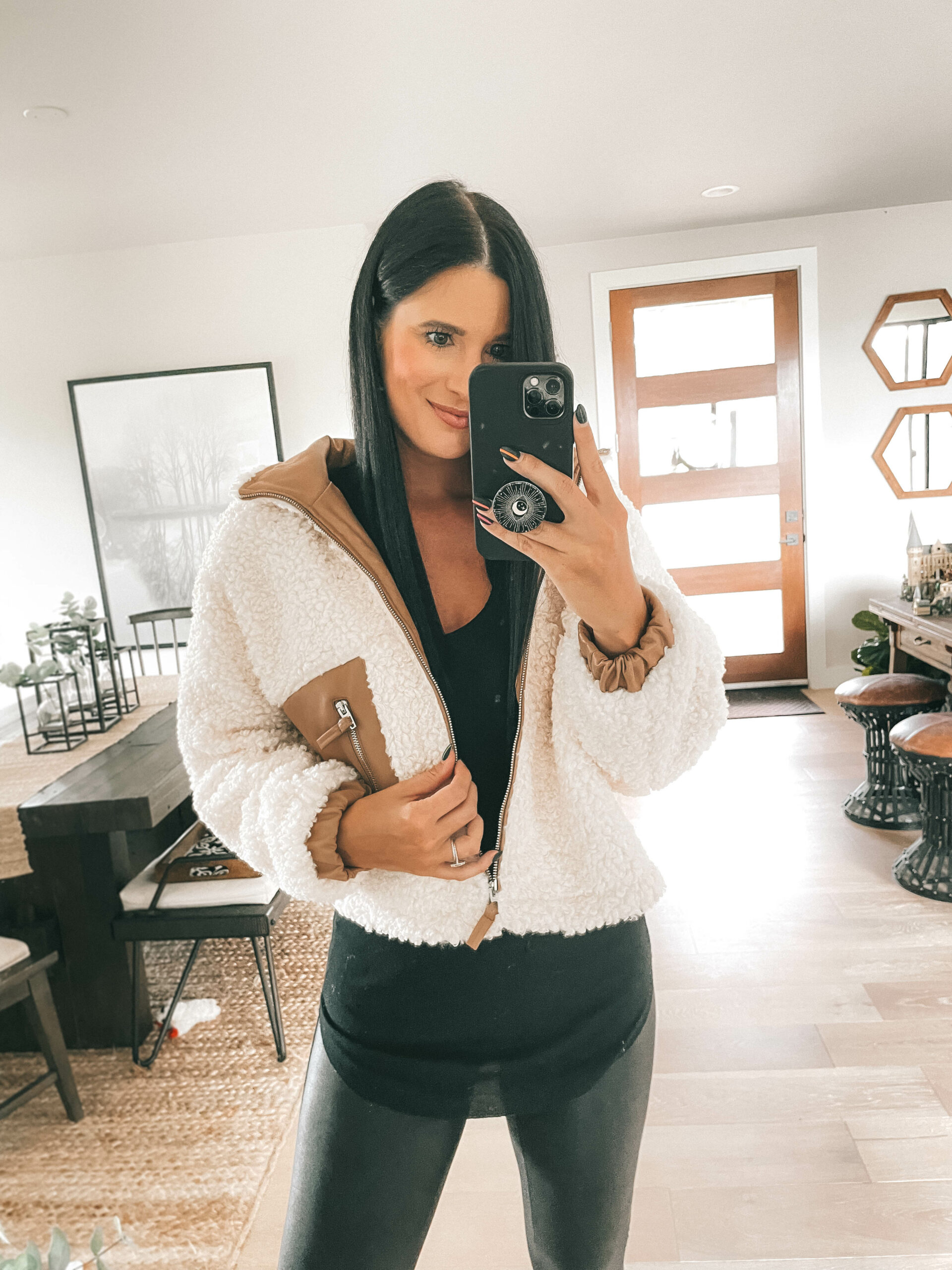 Nordstrom Anniversary Sale by popular Austin fashion blog, Dressed to Kill: image of a woman wearing a cream fleece jacket, black top, and black faux leather leggings.