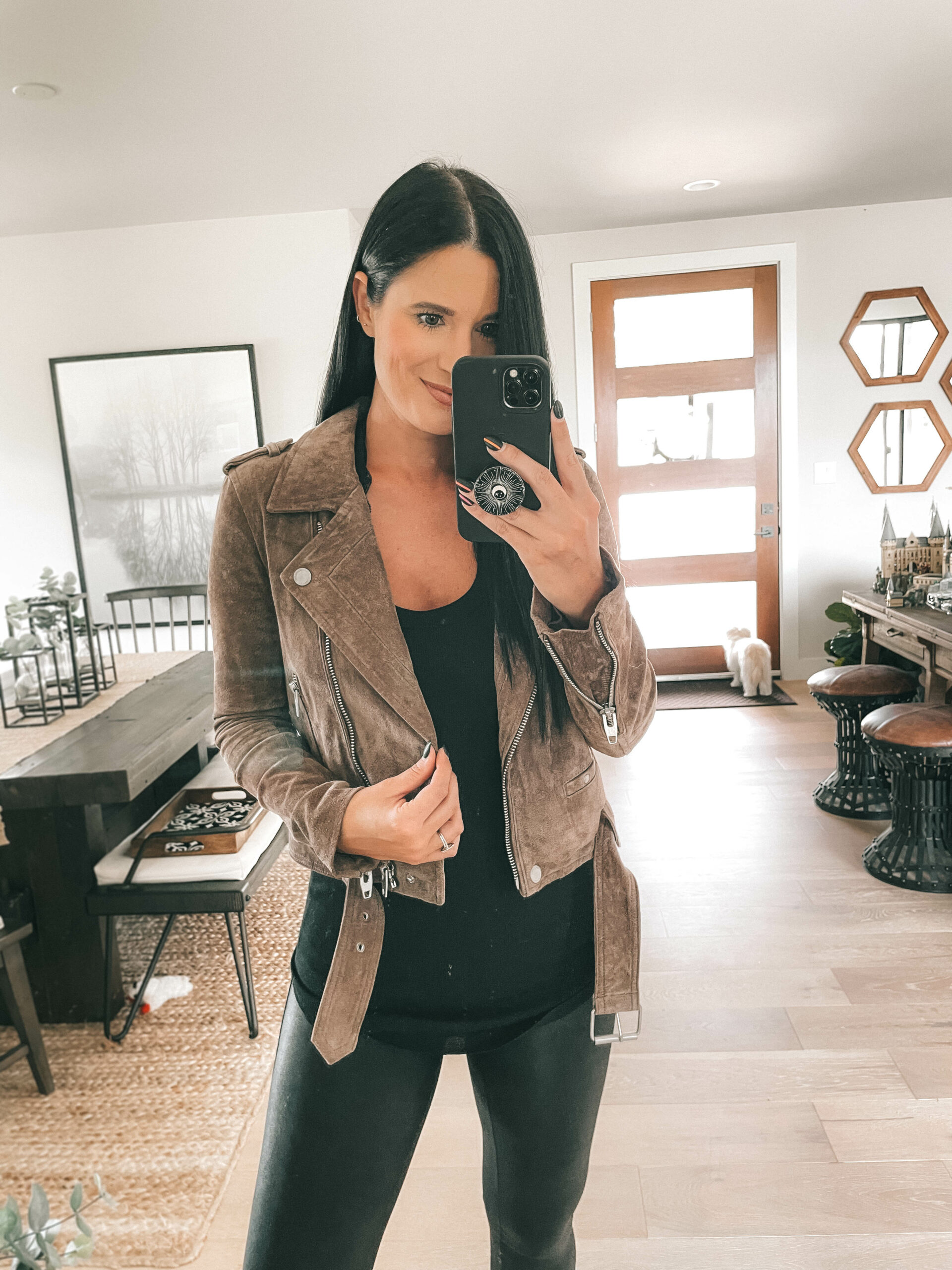 Nordstrom Anniversary Sale by popular Austin fashion blog, Dressed to Kill: image of a woman wearing a brown suede jacket, black top, and black faux leather leggings.