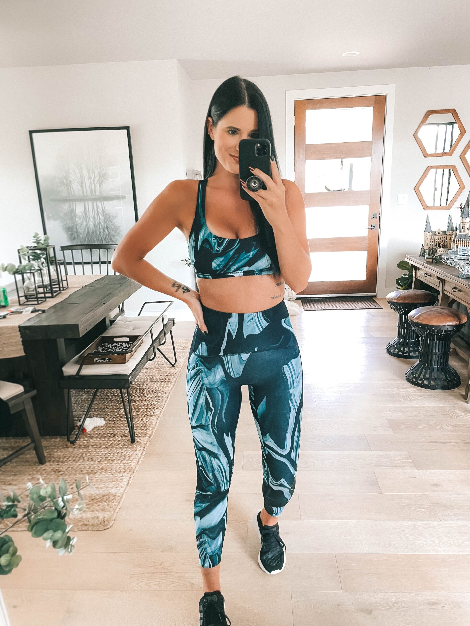 Nordstrom Anniversary Sale by popular Austin fashion blog, Dressed to Kill: image of a woman wearing a blue and black sports bra and blue and black leggings with a pair of black athletic sneakers.