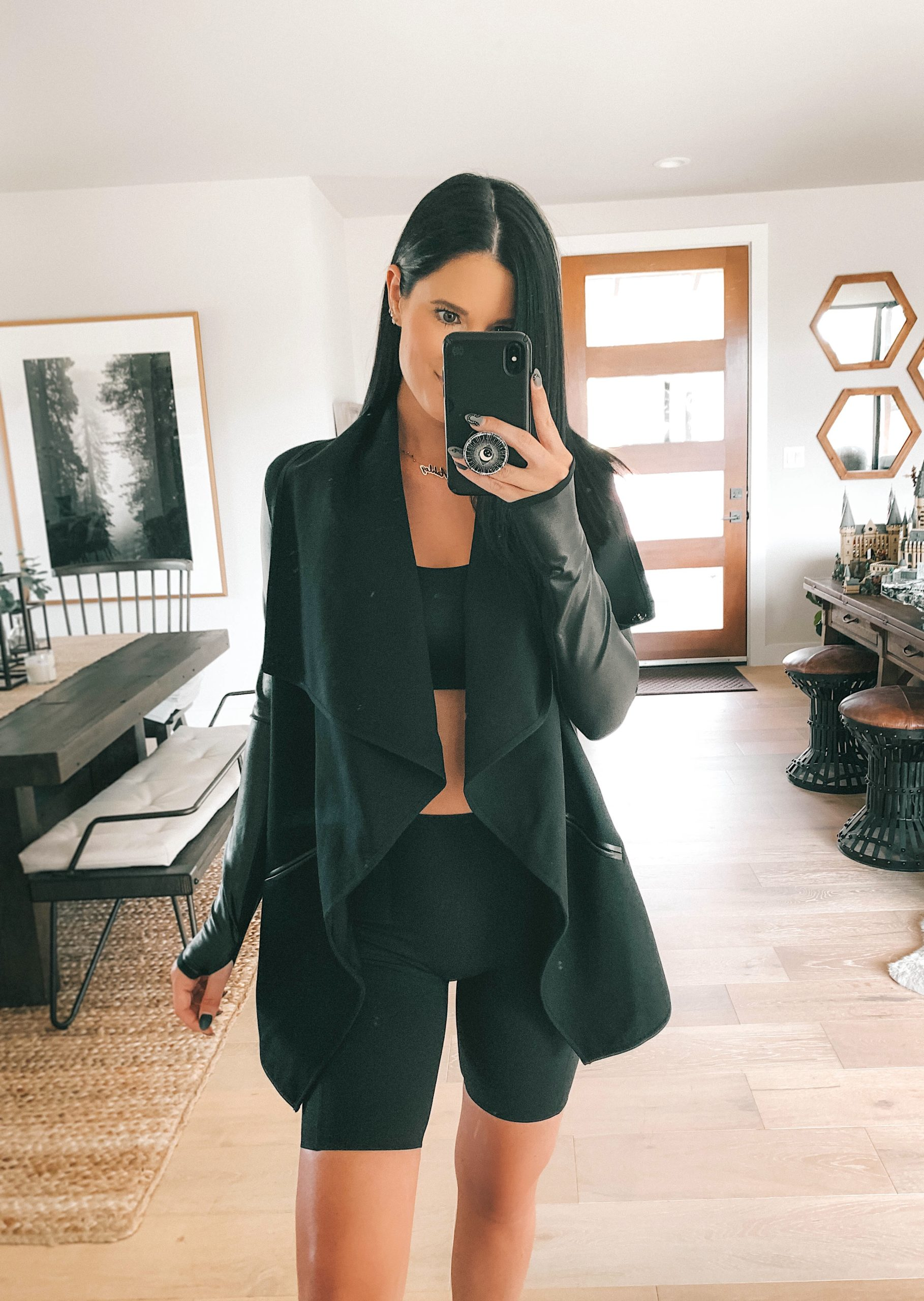 Nordstrom Anniversary Sale by popular Austin fashion blog, Dressed to Kill: image of a woman wearing a black cardigan with a black sports bra and black biker shorts.