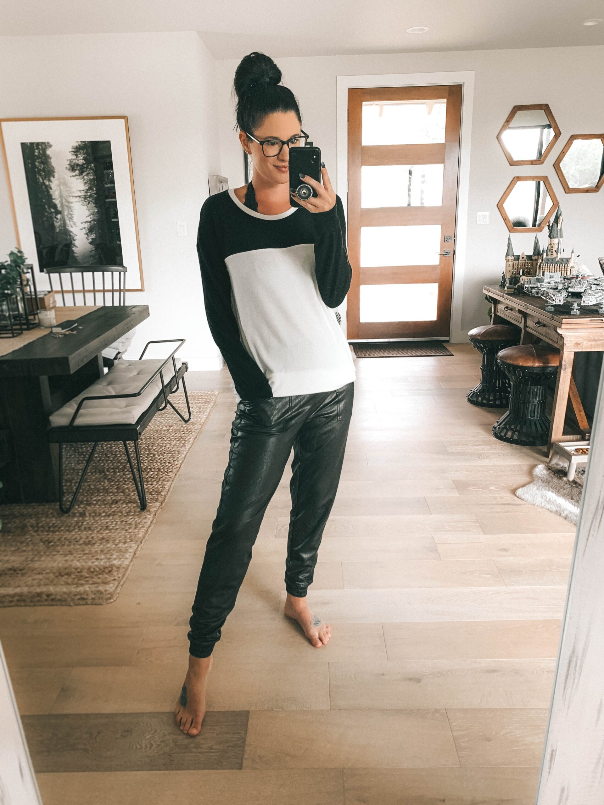Nordstrom Anniversary Sale by popular Austin fashion blog, Dressed to Kill: image of a woman wearing a black and white color block shirt and black faux leather jogger pants.